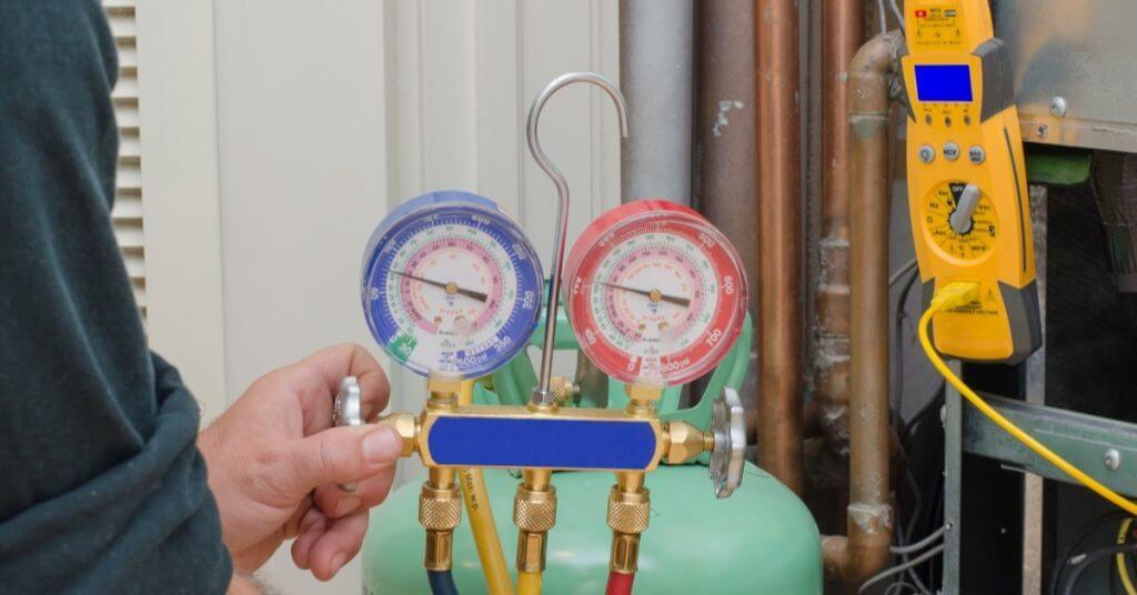 HVAC technician adjusting refrigeration guages