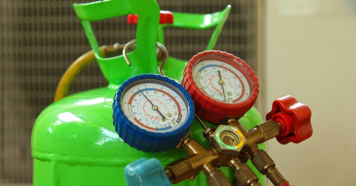 HVAC gauges resting on a tank of refrigerant
